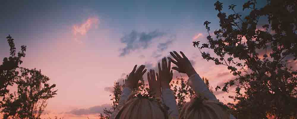 Two blonde women reach their hands out to a sunset sky