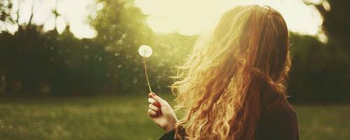 Girl blowing dandelion seeds into the wind