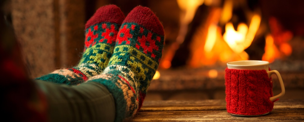 Feet in fuzzy socks propped on a coffee table in front of a lit fireside.