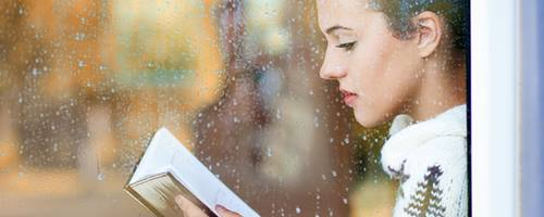 Young woman reading behind a rain-spotted window