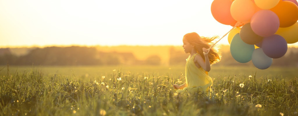 Young girl in yellow dress running through field at sunset with large bouquet of balloons.
