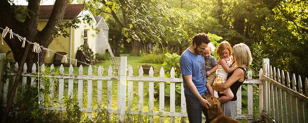 Family in Yard with White Picket Fence