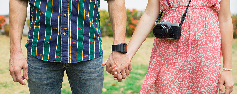 Couple holding hands with camera