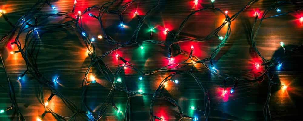 String of holiday lights lit against wood floorboards