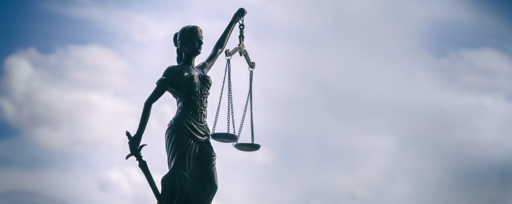 A statuette of Justice holding law scales against a blue sky.
