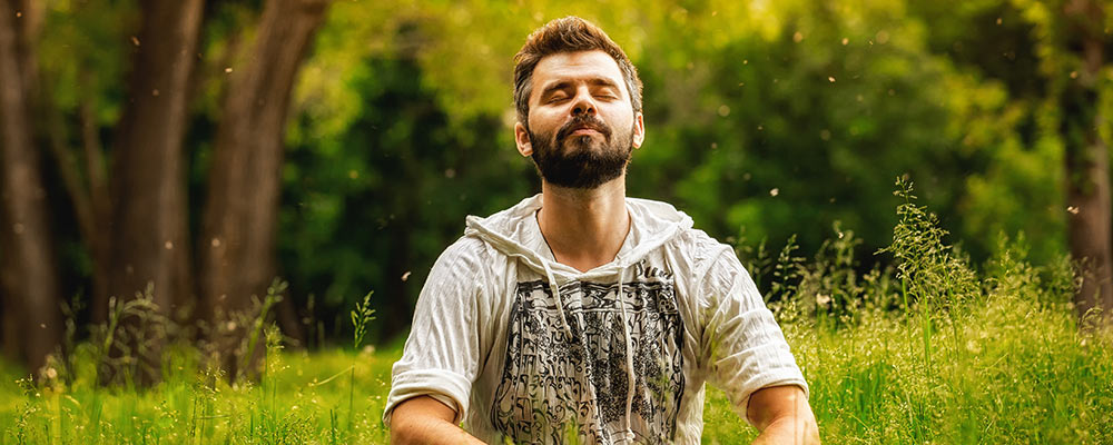 Man meditating in a meadow