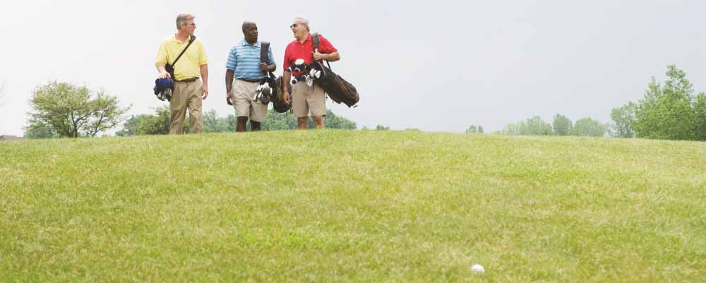 Three older men on a green golf course