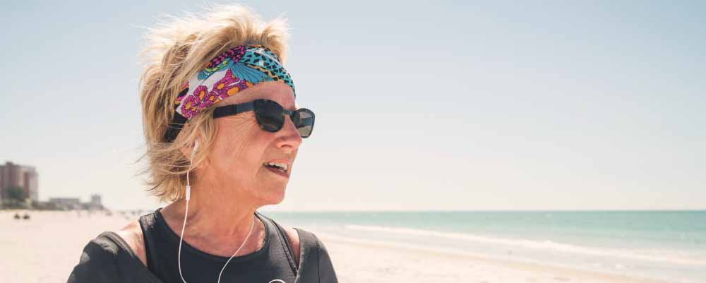 Older woman on beach with earbuds and colorful bandana