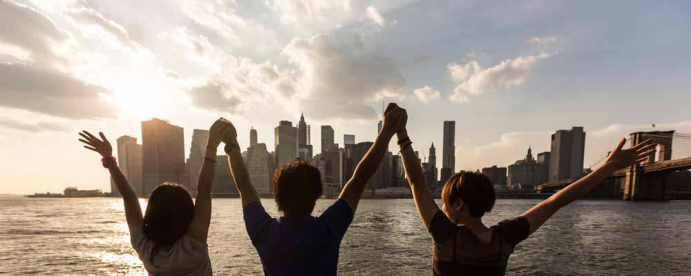 Three people with their hands raised with city skyline in the background