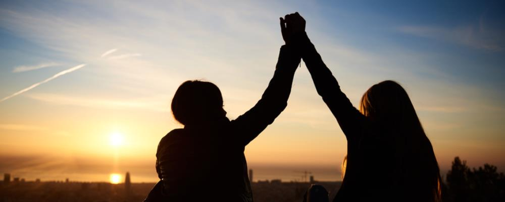 Sihouette of two people high-fiving in the sunrise