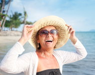 Elder woman at beach with hat on