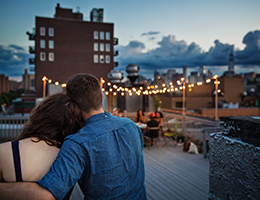 Man and woman at a rooftop party.