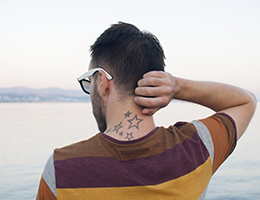 Back of young man with neck tattoo.