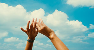 Hands in air, blue sky and clouds.