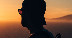 Man with hat watching sunset near lake.